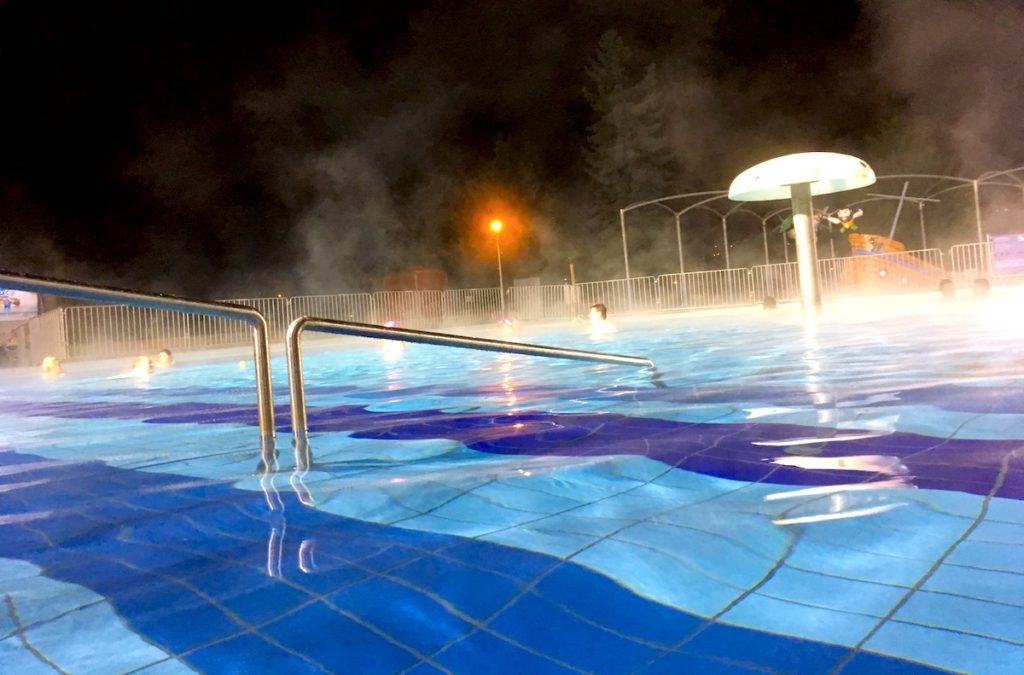 The outdoor thermal pool steaming on a winter evening